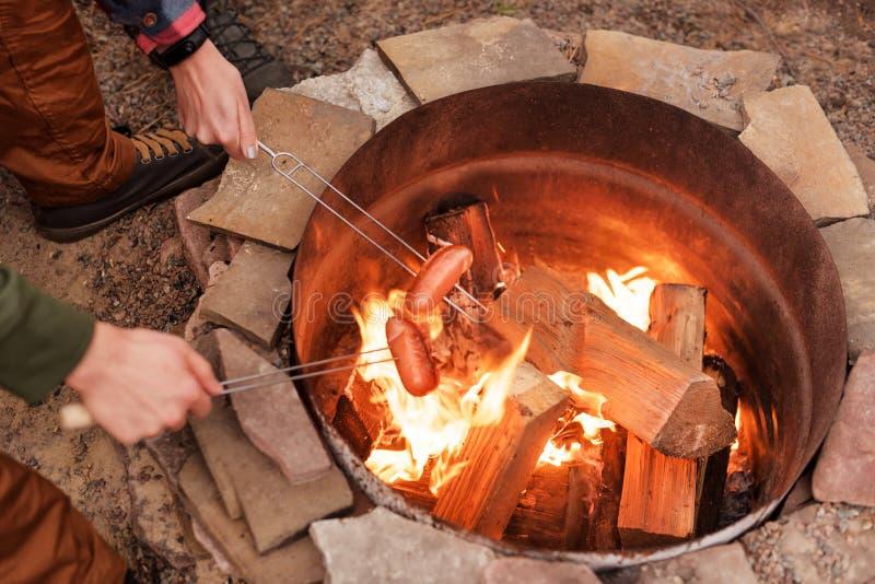 Piec na grillu kiełbasy nad ogniskiem, obozowicze piec kiełbasy na wznosić toast rozwidlają Pożarniczy miejsce, przyjaciele, tury zdjęcia royalty free