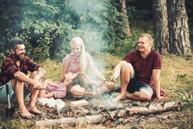 Piec na grillu kiełbasy nad ogniskiem, obozowicze piec kiełbasy na wznosić toast wtykają Pożarniczy miejsce z przyjaciółmi lub tu zdjęcie stock