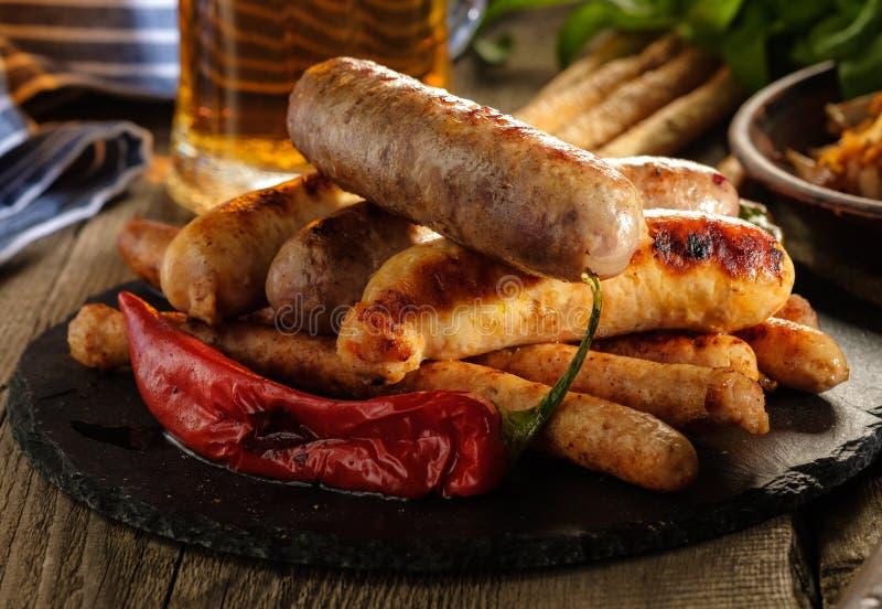 Piec na grillu kiełbasy z szkłem piwo na drewnianym stole wieśniak fotografia stock