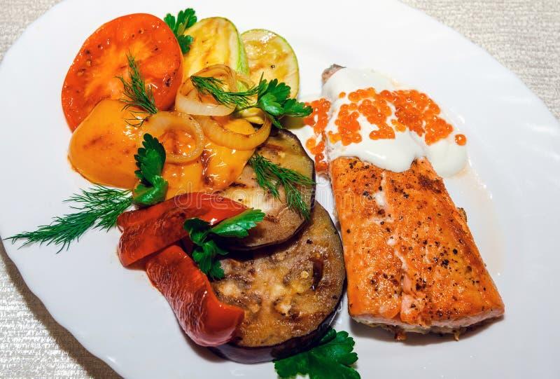 Piec na grillu kość stek przyprawiający z pikantność, świeżych ziele świeżym pomidorem, pieczonymi grulami i gorącymi chili piepr obraz stock