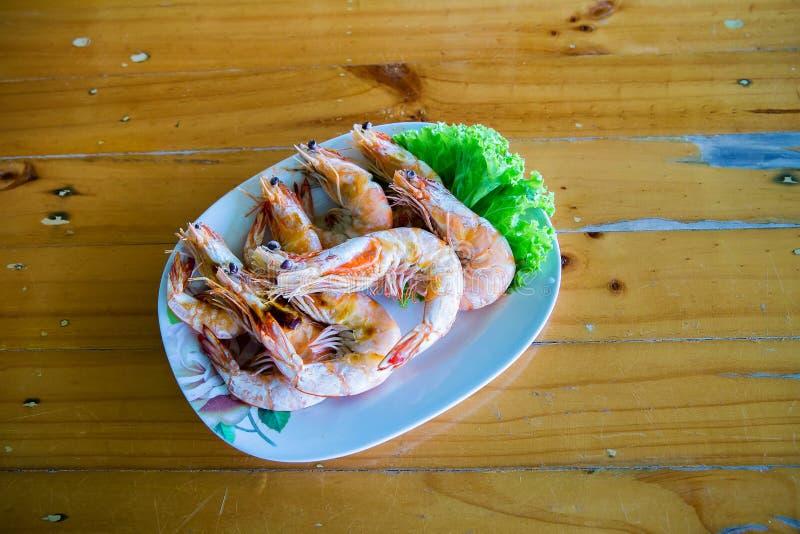 Piec na grillu krewetki na błękitnym naczyniu, umieszczającym na drewno stole Owoce morza menu obrazy royalty free