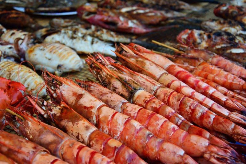 Piec na grillu krewetki i inny owoce morza wystawiający w noc rynku zdjęcie stock