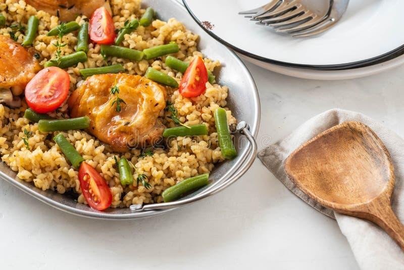 Piec na grillu kurczaków uda z bulgur, szparagowymi fasolami i pomidorami, smakowity lunch Podoła przestrzeń zdjęcia stock