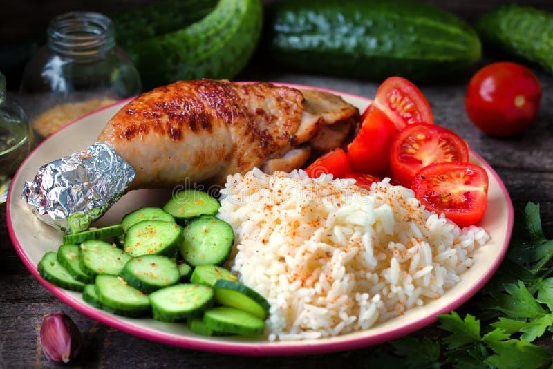 Piec na grillu kurczak noga, biali ryż, slised ogórek z sezamowymi ziarnami, tomtoes i ziele, obrazy royalty free