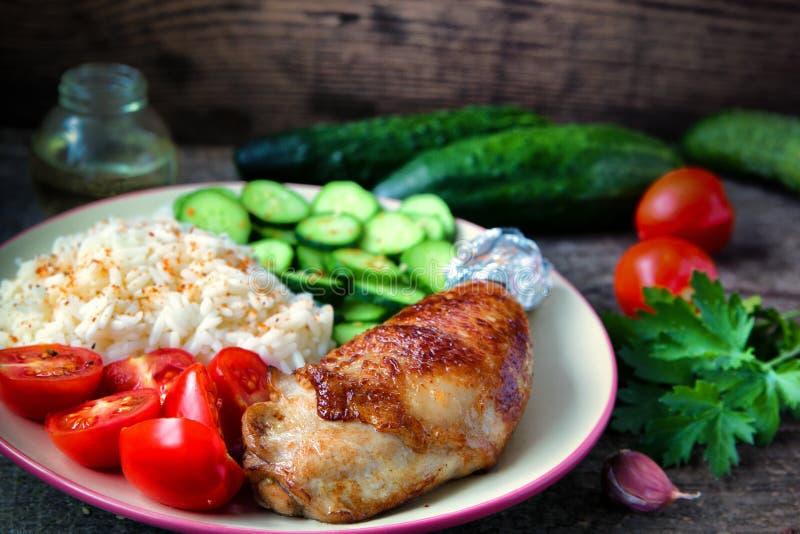 Piec na grillu kurczak noga, biali ryż, slised ogórek z sezamowymi ziarnami, tomtoes i ziele, obraz royalty free