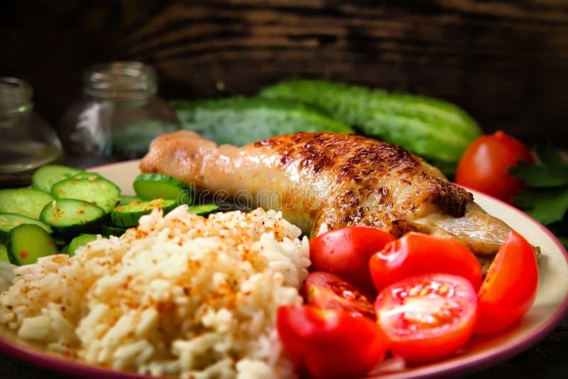 Piec na grillu kurczak noga, biali ryż, slised ogórek z sezamowymi ziarnami, tomtoes i ziele, obrazy stock