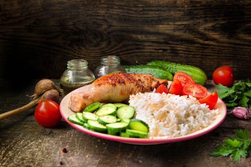 Piec na grillu kurczak noga, biali ryż, slised ogórek z sezamowymi ziarnami, tomtoes i ziele, zdjęcie stock