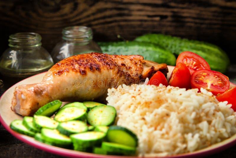 Piec na grillu kurczak noga, biali ryż, slised ogórek z sezamowymi ziarnami, tomtoes i ziele, obraz stock