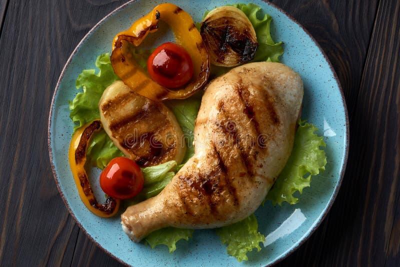 Piec na grillu kurczak noga z warzywami na błękitnym talerzu zdjęcia royalty free