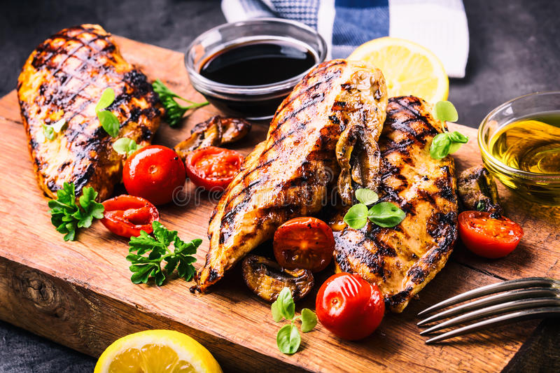 Piec na grillu kurczak pierś w różnych różnicach z czereśniowymi pomidorami, pieczarkami, ziele, rżniętą cytryną na drewnianej de zdjęcie stock