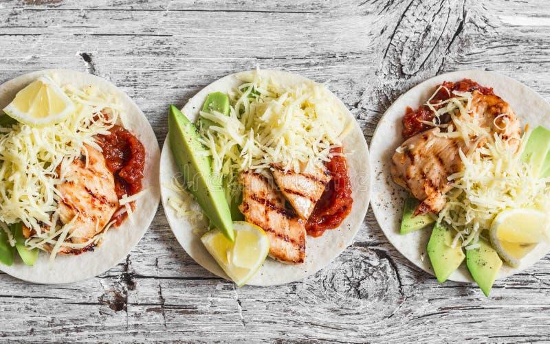 Piec na grillu kurczaka, avocado, serowych i korzennych pomidorowego kumberlandu tortillas na drewnianym nieociosanym tle, zdjęcie royalty free