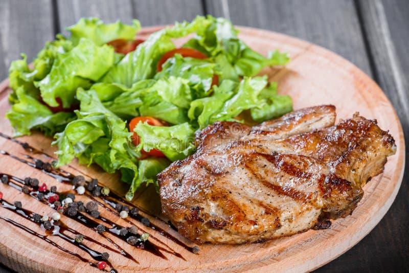 Piec na grillu kurczaka mięso z sałatką, pomidorami i kumberlandem na drewnianej tnącej desce świeżego warzywa, zdjęcia royalty free
