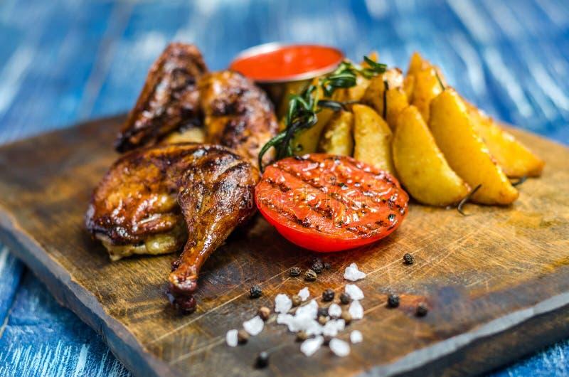 Piec na grillu kurczaka nogi, pomidory i grule, obraz royalty free