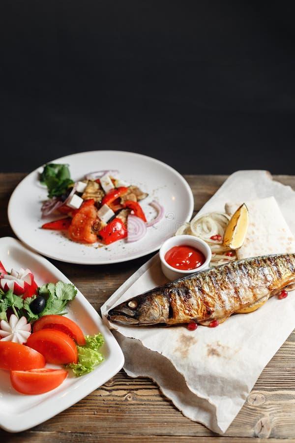 Piec na grillu makrela i sałatka świezi warzywa Słuzyć na drewnianej desce na nieociosanym stole Grill restauraci menu zdjęcia stock