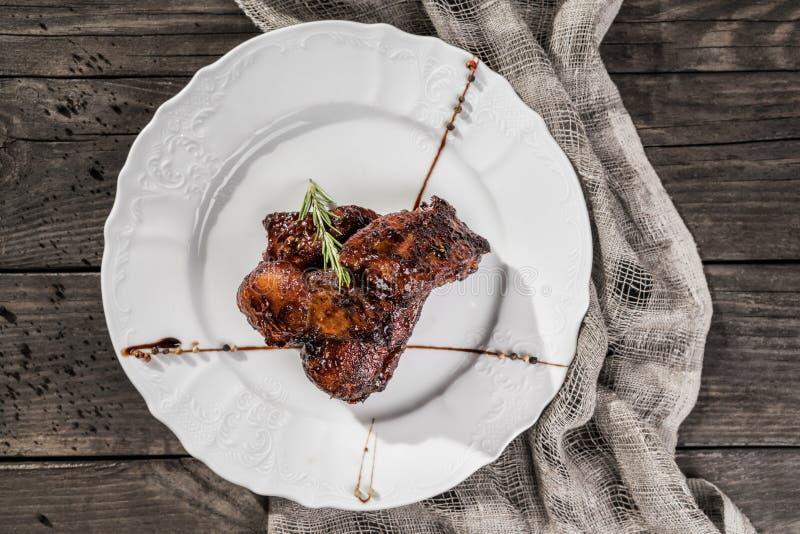 Piec na grillu mięsny stek z rozmarynami na talerzu nad nieociosanym drewnianym tłem rozdaje gorącego mięso obraz stock
