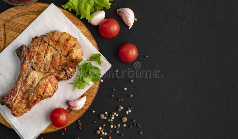 piec na grillu mi?so kopii przestrze?, zmrok powierzchnia, ziele, sa?ata, pomidor, czarna pikantno?? w drewnianych ?y?kach fotografia stock
