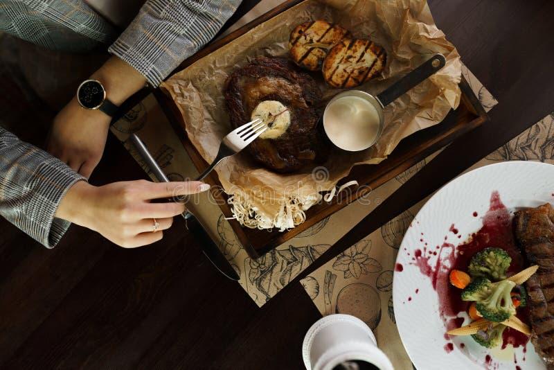 Piec na grillu mięso na warzywach na drewnianym stole w restauracji i grillu smakowity lunch żeński zamknięte żeńskie ręki zdjęcie stock