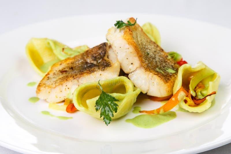 Piec na grillu morszczuk polędwicowy w pikantność i dekoracjach na round talerzu dalej obraz stock