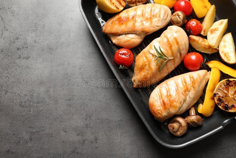 Piec na grillu nieckę z pieczony kurczak piersiami i garnirunek na popielatym tle, odgórny widok obrazy royalty free