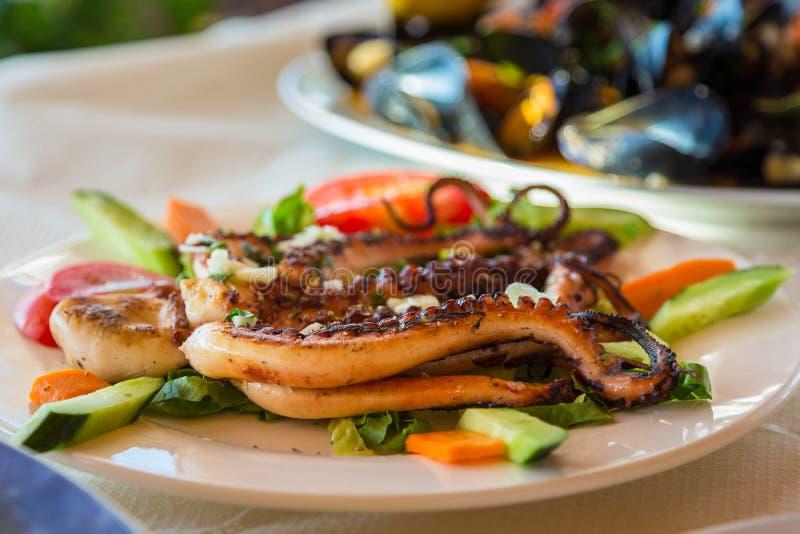 Piec na grillu ośmiornica na białym talerzu z warzywami zdjęcia royalty free