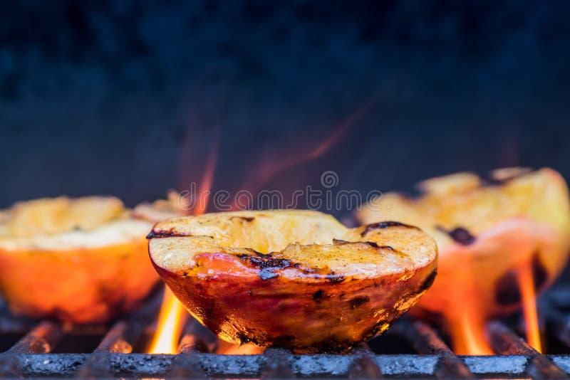 Piec na grillu płomienie i brzoskwinie zdjęcie royalty free