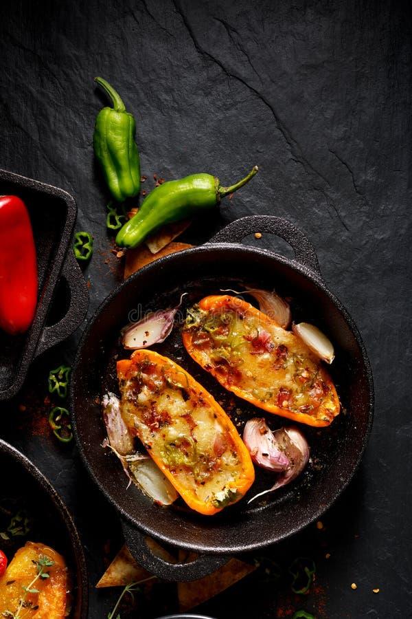 Piec na grillu pieprze faszerowali z serem, bekonem, warzywami i ziele na czarnym tle, fotografia stock