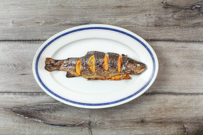 Piec na grillu pstrąg na białym owalu talerzu z błękitnym obręczem zdjęcia royalty free