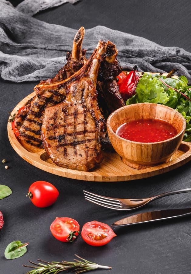 Piec na grillu Ribeye stek na ko?ci i warzywa z ?wie?? sa?atk? i bbq kumberlandem na tn?cej desce nad czerni? drylujemy t?o gor?c zdjęcie royalty free