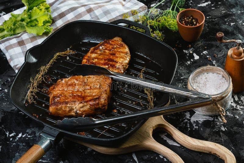 Piec na grillu ribeye wołowiny stek na żelaznej niecce z ziele i pikantność Odgórny widok z kopii przestrzenią dla twój teksta fotografia royalty free