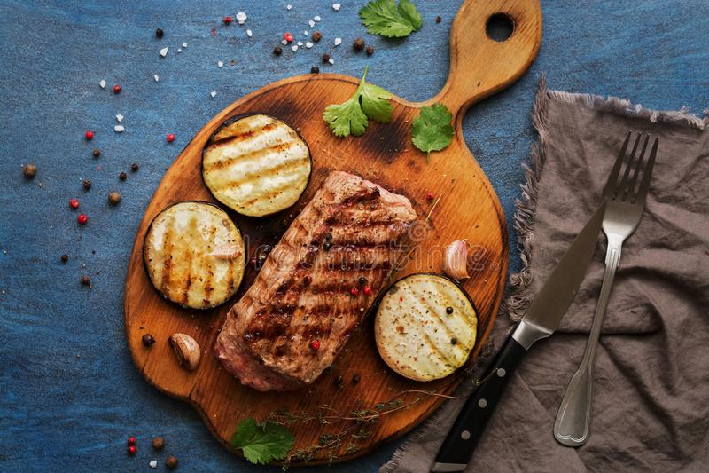 Piec na grillu ribeye wołowiny stek, ziele i pikantność na błękitnym nieociosanym tle, Odgórny widok, mieszkanie nieatutowy zdjęcia stock