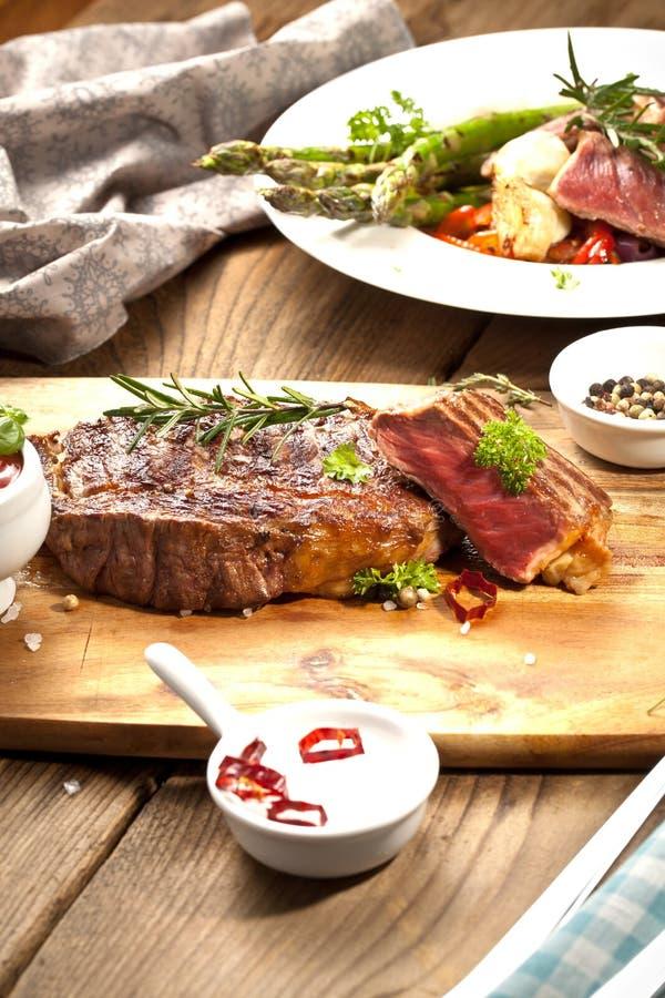 Piec na grillu ribeye wołowiny stek, ziele i pikantność, Odgórny widok fotografia stock