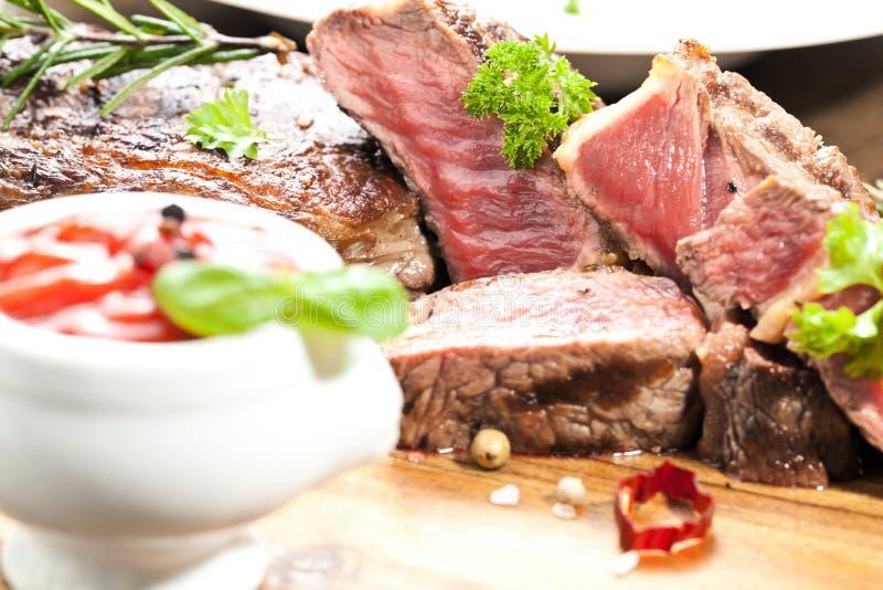 Piec na grillu ribeye wołowiny stek, ziele i pikantność, Odgórny widok zdjęcie stock