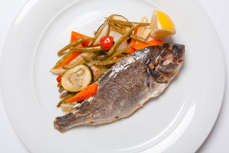 Piec na grillu rybi z piec warzywami na talerzu fotografia stock