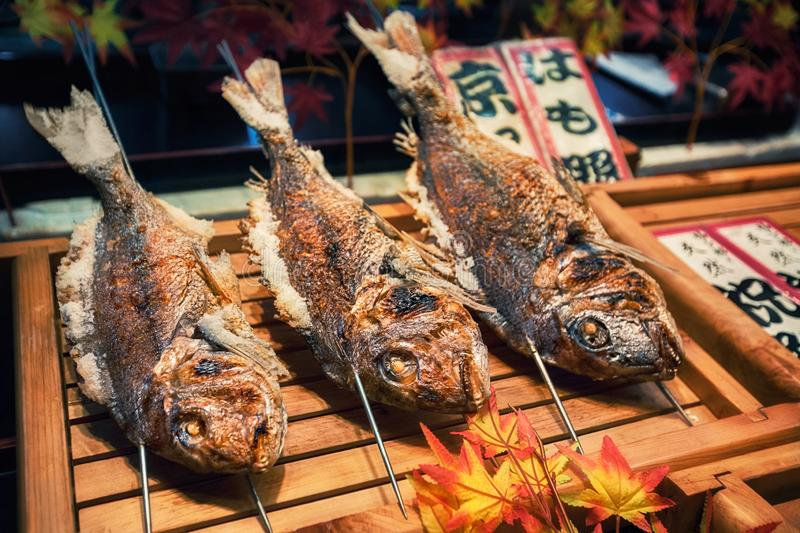 Piec na grillu ryby na kijach jako uliczny jedzenie przy Nishiki rynkiem, Kyoto, Japonia fotografia stock