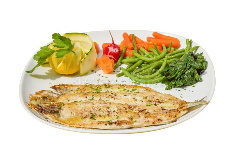 Piec na grillu seabass fith z cytryną, pomidorem i gotującymi się warzywami na białym tle, zdjęcia stock