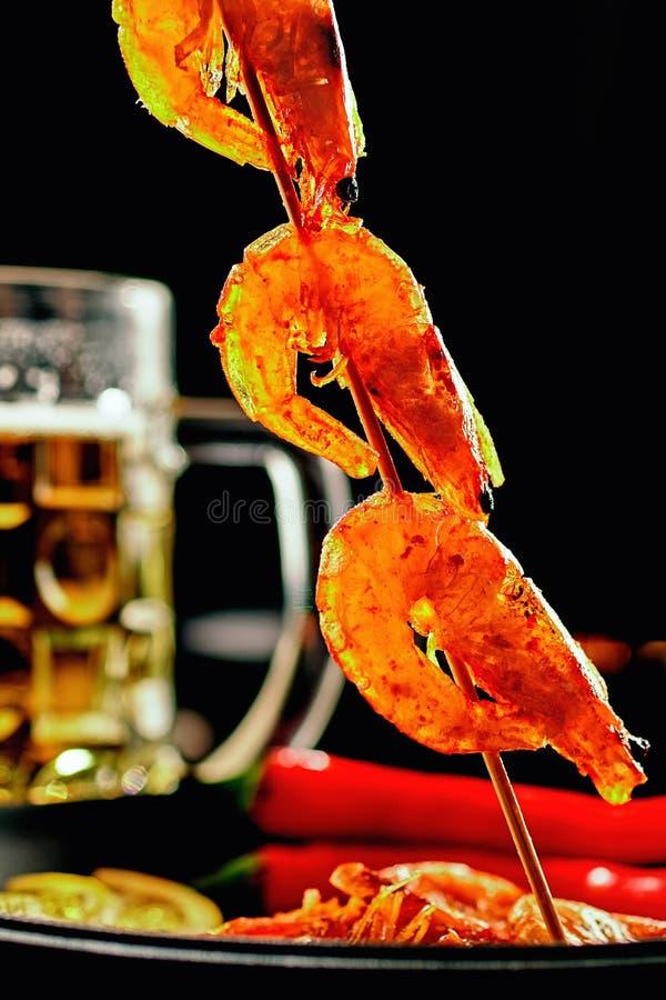 Piec na grillu smażył garnele na drewnianych skewers Tło kubka piwo, żeliwna smaży niecka z grill garnelami, czerwony pieprz, cyt zdjęcie stock