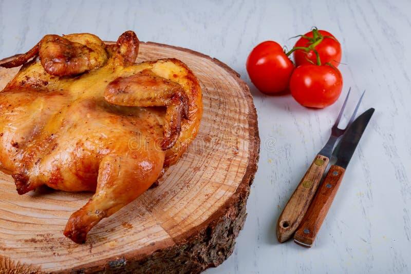 Piec na grillu smażył pieczonego kurczaka tytoniu i surowych pomidorów na drewnianej desce zdjęcie royalty free