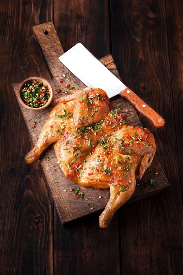 Piec na grillu smażył pieczonego kurczaka tytoniu na tnącej desce na ciemnym drewnianym tle obrazy stock