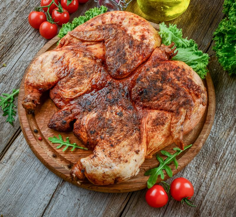 Piec na grillu smażył pieczonego kurczaka tytoniu na tnącej desce fotografia stock