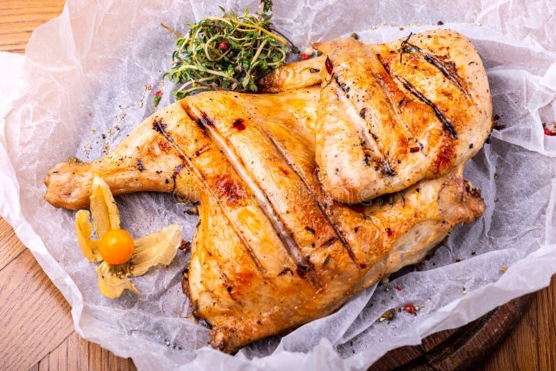 Piec na grillu smażył pieczonego kurczaka tytoniu na tnącej desce z ziele na drewnianym tle obraz royalty free