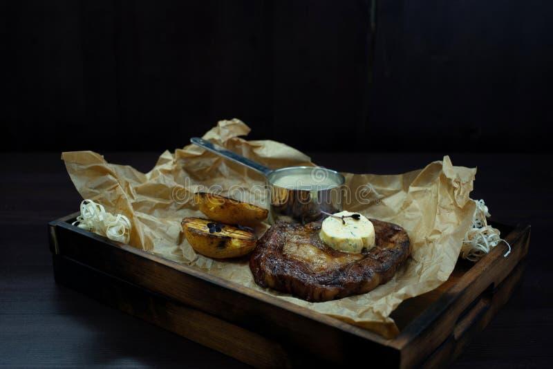 Piec na grillu soczysty stek z masłem i plasterkami piec oberżyna na rocznik deski stojakach na drewnianym stole przeciw ciemnemu fotografia royalty free
