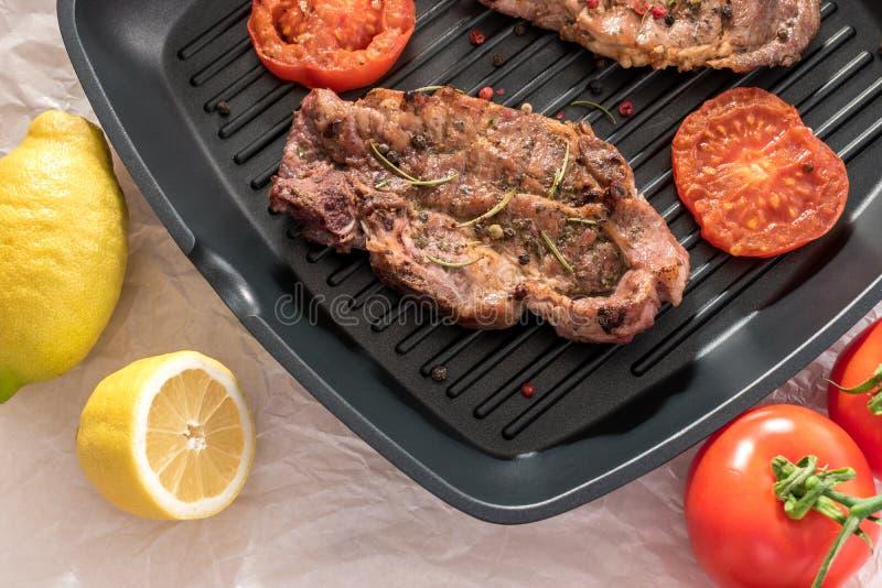Piec na grillu stek na grill niecce z pomidorami i cytryną fotografia royalty free
