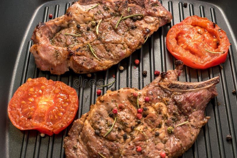 Piec na grillu stek na grill niecce z pomidorami i pikantność zdjęcie stock