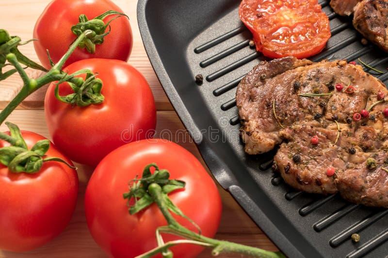 Piec na grillu stek na grill niecce z pomidorami i pikantność obrazy stock