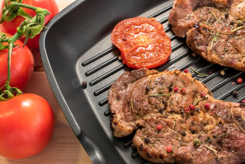 Piec na grillu stek na grill niecce z pomidorami i pikantność obrazy royalty free