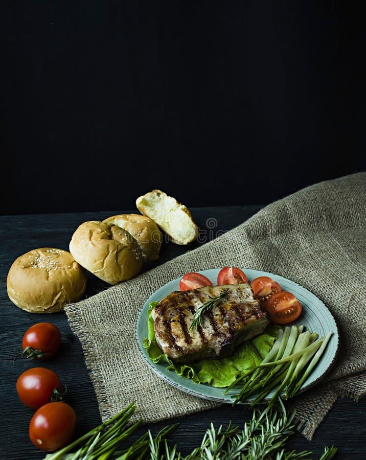 Piec na grillu stek s?uzy? na talerzu, dekoruj?cym z pikantno?? dla mi?sa, rozmaryn?w, zieleni i warzyw na ciemnym drewnianym tle zdjęcia royalty free