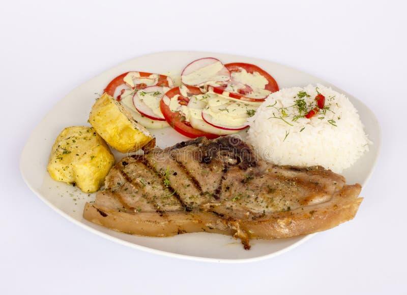 Piec na grillu stek wieprzowiny mięso z sałatką, ryż, grule, pomidory słuzyć z szkłem chicha zdjęcie stock