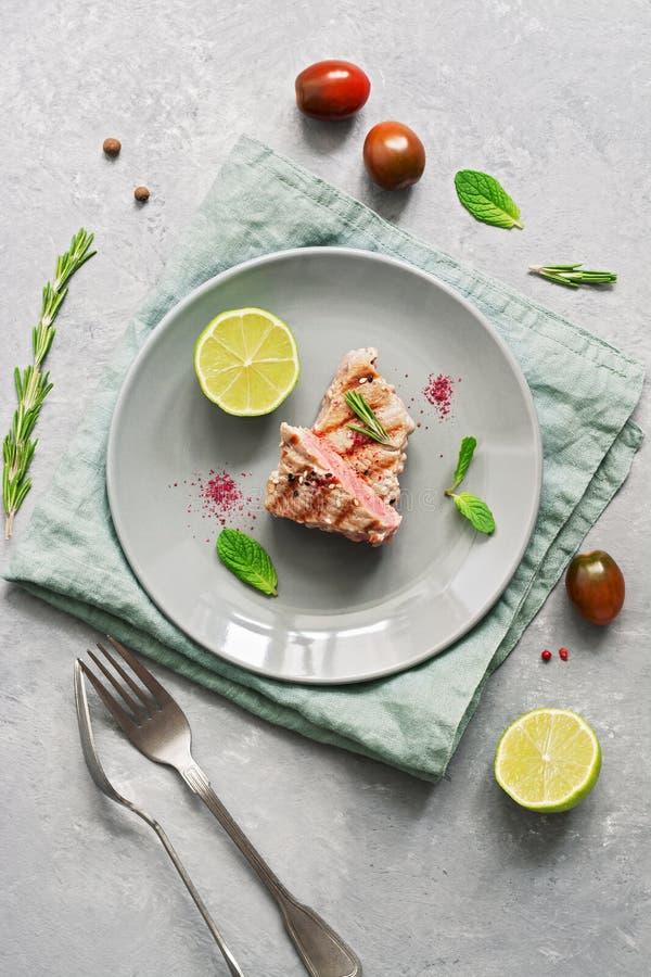 Piec na grillu stku tuńczyka ryba z wapnem na szarym tle Odgórny widok, mieszkanie nieatutowy fotografia stock