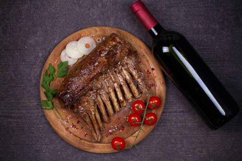 Piec na grillu stojak baranek w kumberlandzie, szkle i butelce wino balsamic octu i brown cukieru, Jagnięcy kotleciki z warzywami zdjęcia royalty free