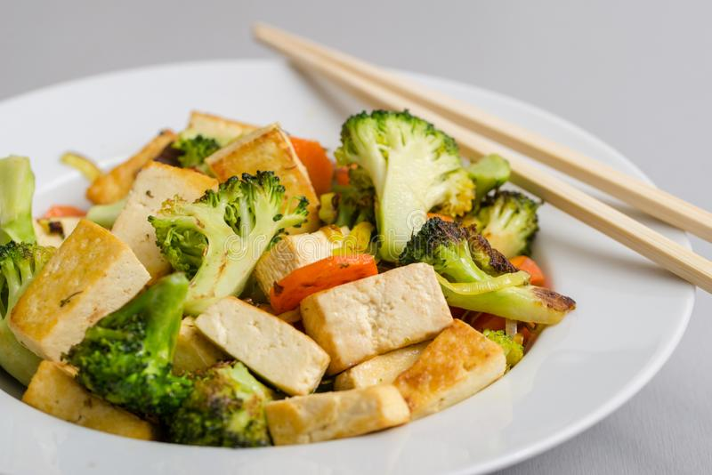 Piec na grillu tofu z brokułami i marchewkami w bielu talerzu z chopsticks na prawej stronie obrazy royalty free